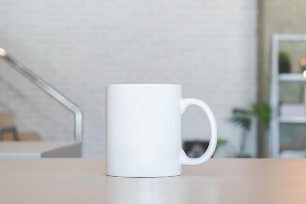 Tazza bianca sul tavolo e sullo sfondo camera moderna