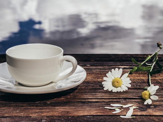 Tazza bianca vuota con i fiori di primavera