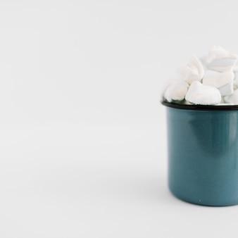 Tazza blu con marshmallow sul tavolo