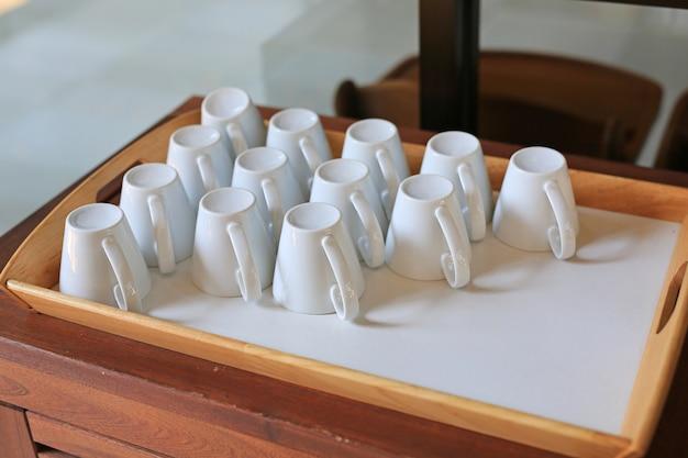 Tazza capovolta per caffè sul vassoio di legno.