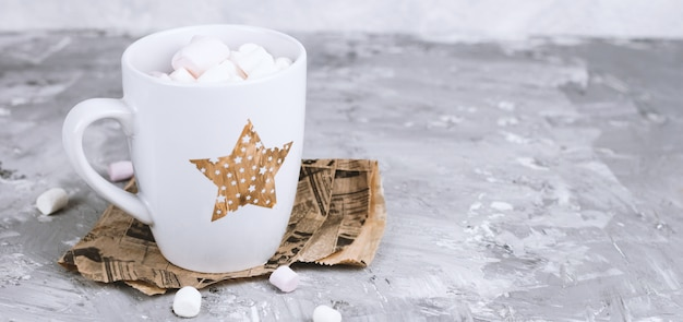 Tazza carina con marshmallow su un cemento grigio grunge