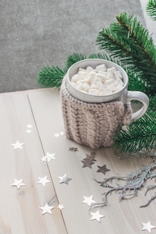 Tazza carina piena di marshmallow circondato da decorazioni natalizie sul tavolo