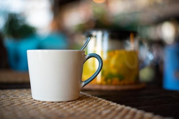 Tazza ceramica del primo piano sulla tavola di legno sul fondo di vetro della teiera con tisana, l'olivello spinoso e la menta
