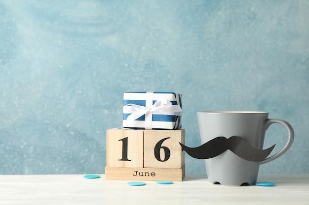 Tazza con baffi decorativi, confezione regalo e calendario in legno sul tavolo bianco su sfondo blu, spazio per il testo