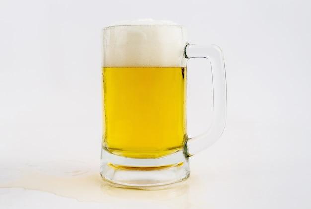 Tazza con birra su sfondo bianco