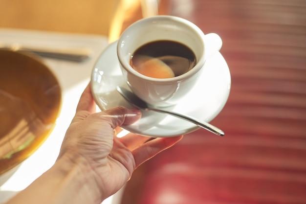 Tazza con caffè del mattino in mano femminile
