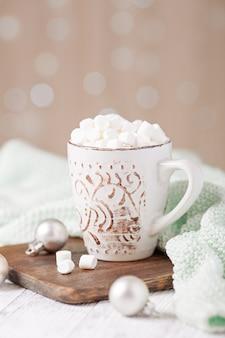 Tazza con caffè e marshmallow, maglione, cannella