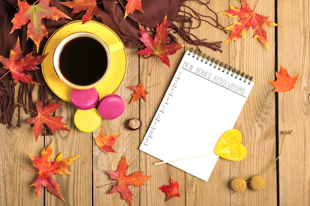 Tazza con caffè nero, lecca lecca, amaretti, sciarpa tessile, blocco note, tavolo in legno con foglie di arancia cadute in autunno