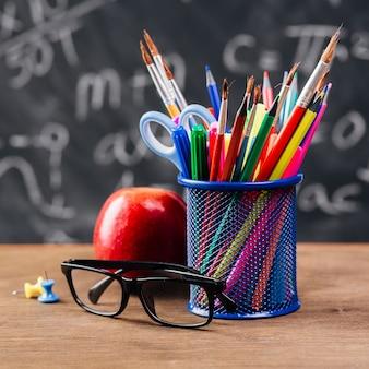 Tazza con cancelleria colorata vicino a bicchieri e mela sul tavolo