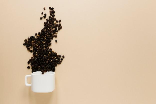 Tazza con chicchi di caffè e copia spazio