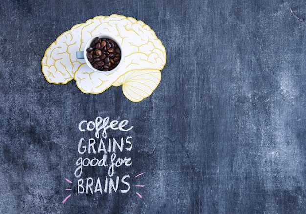 Tazza con chicchi di caffè sul cervello con testo scritto sulla lavagna