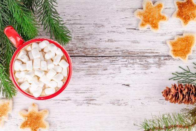 Tazza con cioccolata calda e marshmallow, fette di pane a forma di tostato sul tavolo di legno