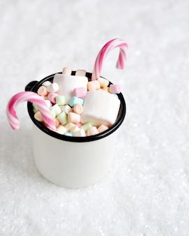 Tazza con cioccolata calda, marshmallow, bastoncini di zucchero sulla neve