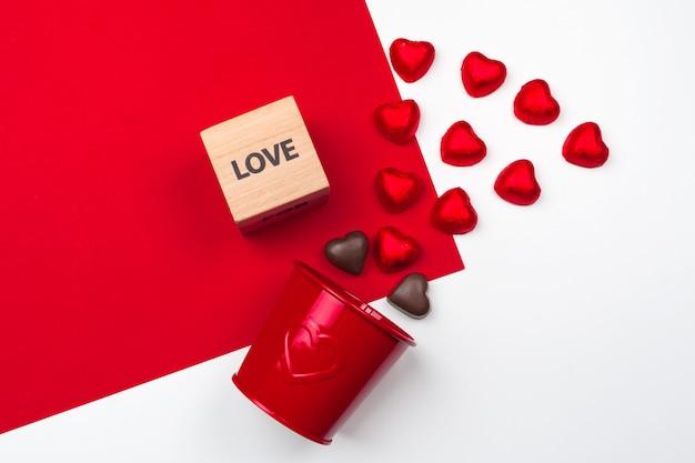 Tazza con cuori di cioccolato sul rosso. composizione piatta laica. romantico, san valentino