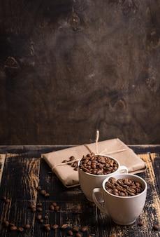 Tazza con i chicchi di caffè a fondo di legno scuro