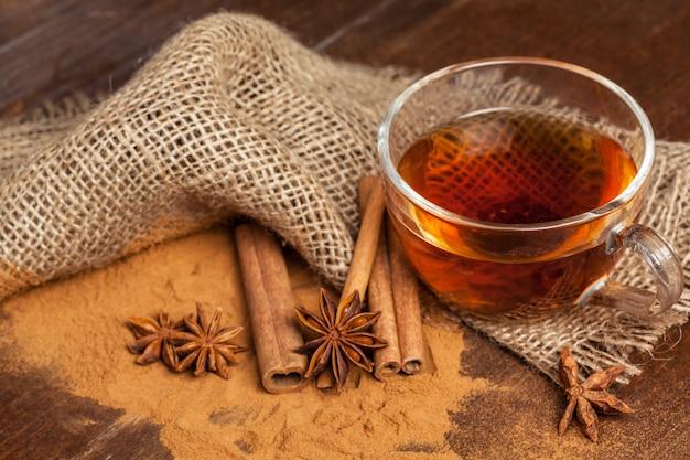 Tazza con il tè di cannella caldo aromatico sulla tavola di legno