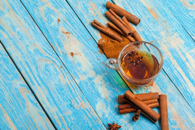 Tazza con tè caldo aromatico alla cannella sul tavolo di legno