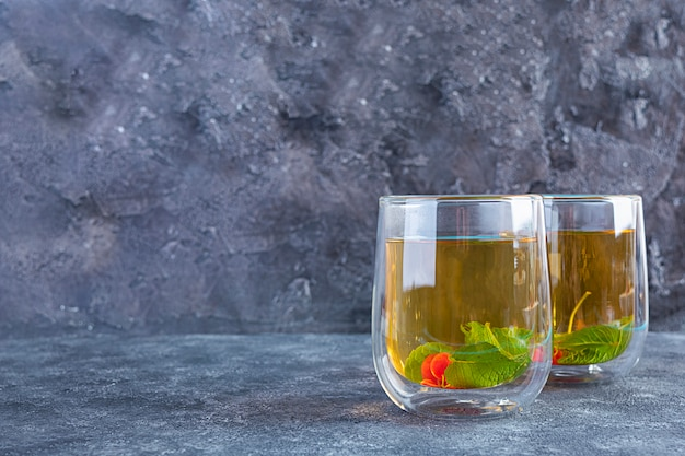 Tazza con tè verde e bacche di menta.