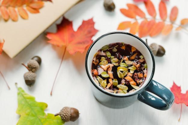 Tazza con tisana nera calda sul tavolo con ghiande e una miscela di acero rosso e foglie tagliate