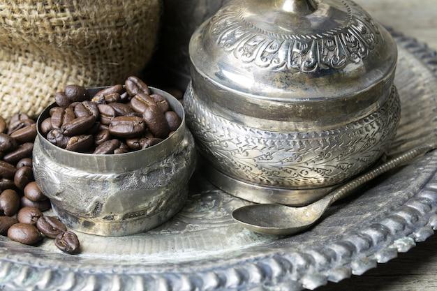 Tazza d'argento e chicchi di caffè nella borsa della tela di sacco su fondo di legno