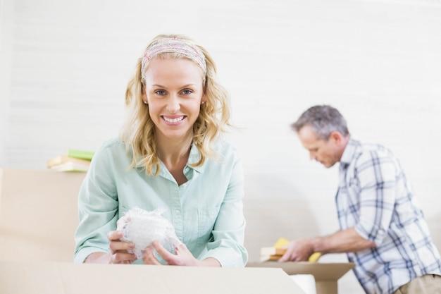 Tazza d'imballaggio sorridente della donna in una scatola con suo marito dietro lei