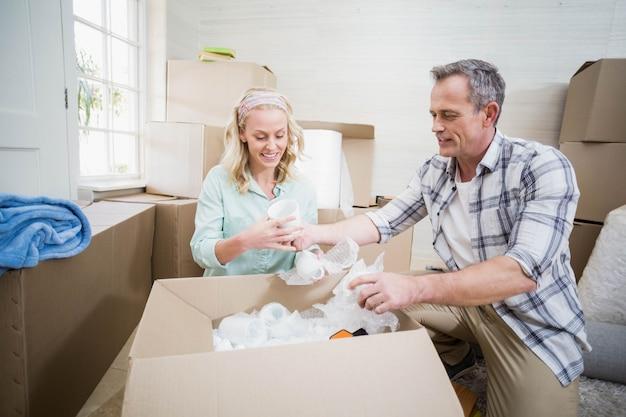 Tazza d'imballaggio sorridente delle coppie in una scatola a casa