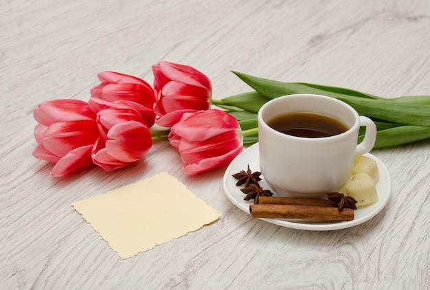 Tazza da caffè con spezie, nota pulita, tulipani rosa su un legno