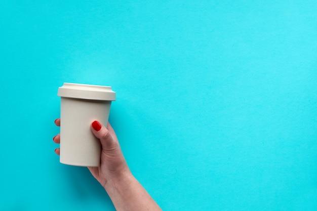 Tazza da caffè in bambù, tenere la tazza o tazza da viaggio in mano femminile. immagine piatta, vista dall'alto con copia-spazio. concetto zero rifiuti con tazza da viaggio eco-friendly.