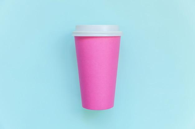 Tazza da caffè in carta rosa di design semplicemente piatto su pastello blu alla moda colorato