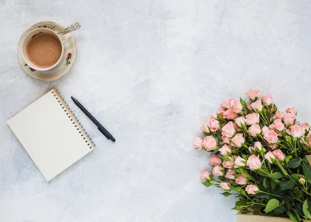 Tazza da caffè in ceramica; blocco note a spirale; bouquet di fiori e penna su sfondo concreto
