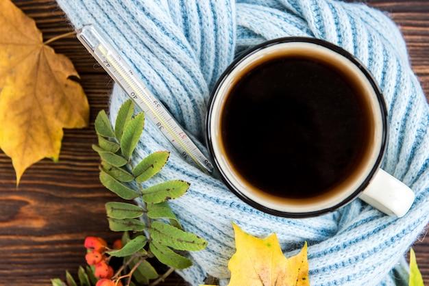 Tazza da tè con sciarpa blu e foglie di autunno su fondo in legno. stagione influenzale in autunno, malattia.