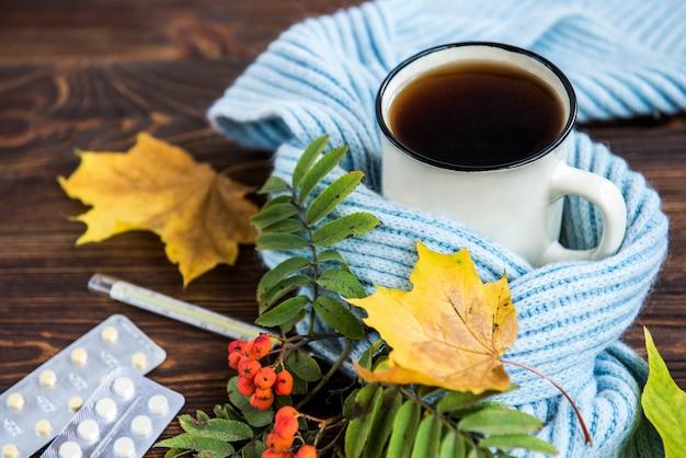 Tazza da tè con termometro, sciarpa blu e foglie di autunno su fondo in legno. stagione influenzale in autunno, malattia.