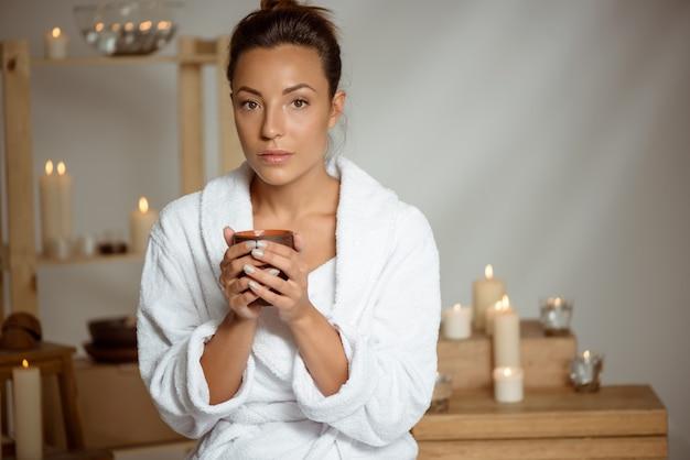 Tazza da tè della tenuta della giovane donna che si rilassa nel salone della stazione termale.