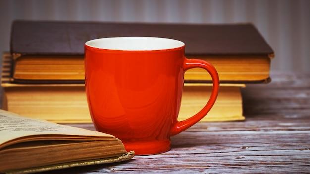 Tazza da tè tra vecchi libri, leggere libri a casa_