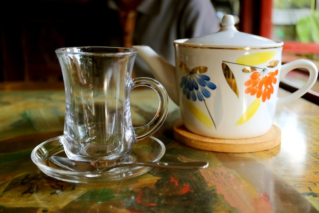 Tazza da tè trasparente con teiera in porcellana sul tavolo