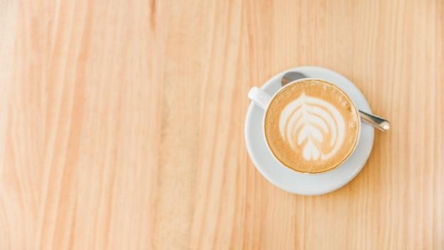 Tazza del caffè del cappuccino con arte latte e cucchiaio su fondo di legno