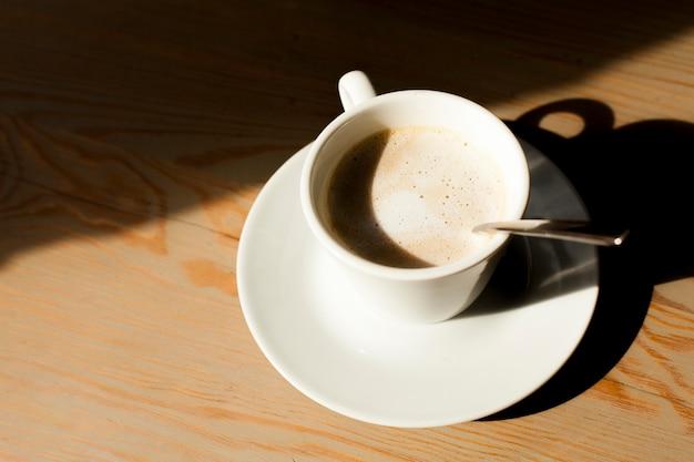 Tazza del caffè del latte con schiuma schiumosa su fondo di legno