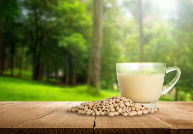 Tazza del latte di soia e fagiolo della soia con il fondo vago astratto della natura della foresta.