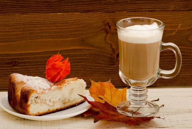 Tazza del latte sulle foglie di autunno e sulla torta di mele