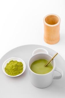 Tazza del primo piano con tè e polvere di matcha