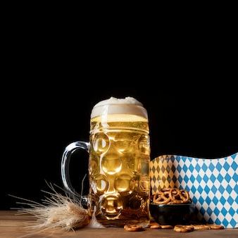 Tazza del primo piano di birra con gli spuntini su una tabella
