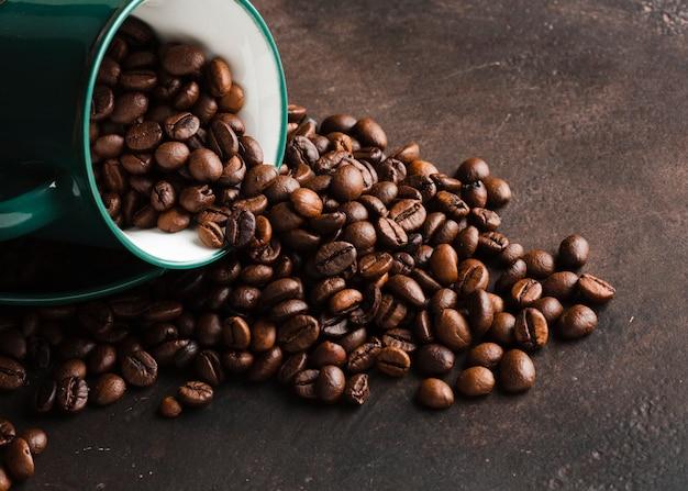 Tazza del primo piano rovesciata con i chicchi di caffè