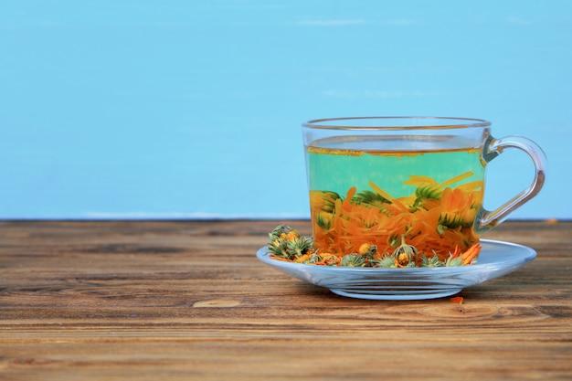 Tazza del tè di calendula su una tavola di legno sul blu