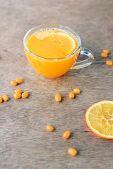 Tazza del tè sano dell'olivello spinoso con l'arancia su una parete di legno.