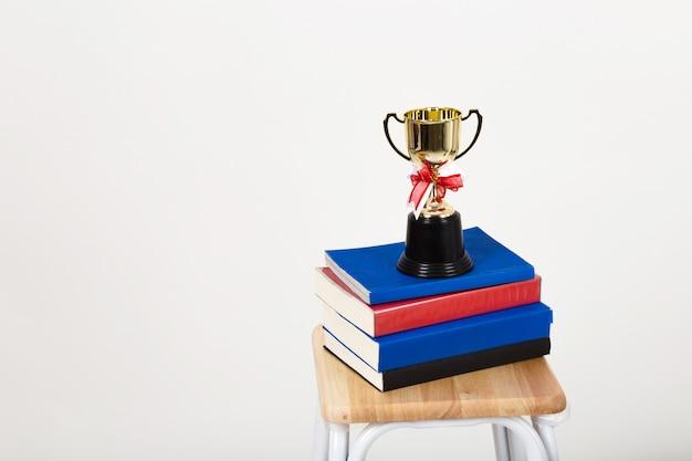 Tazza del trofeo su una pila di libri con copyspace.