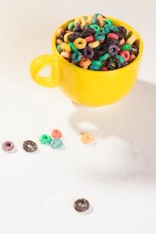 Tazza dell'angolo alto in pieno di cereali sulla tavola