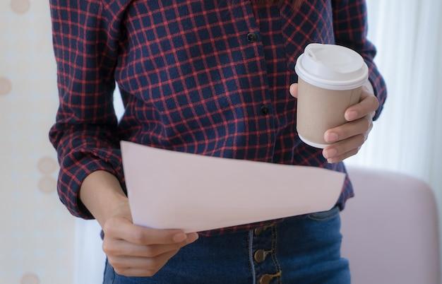 Tazza della carta del giornale della tenuta della donna e della carta del caffè