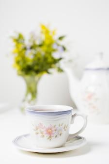Tazza della porcellana di tè e piattino sulla tavola bianca contro fondo selettivo