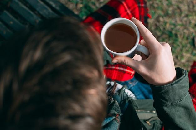 Tazza della tenuta del ragazzo del primo piano con caffè