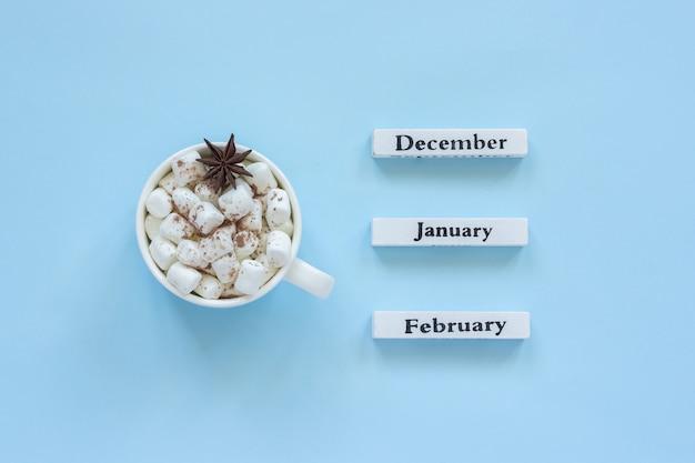 Tazza delle caramelle gommosa e molle del cacao e calendario dicembre gennaio febbraio su fondo blu